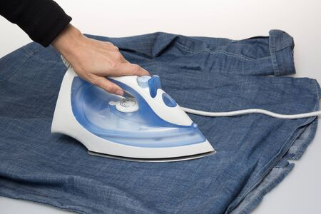 steam iron: Ironing cloth with steam, closeup isolated on white