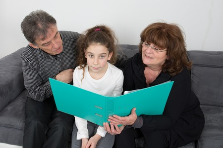 grand daughter: Grand Father  and grand mother helping grand daughter to do their homework in their living room