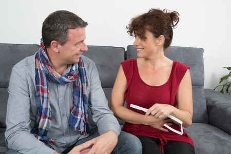 enjoying life: Cheerful loving couple enjoying life at home on sofa Stock Photo