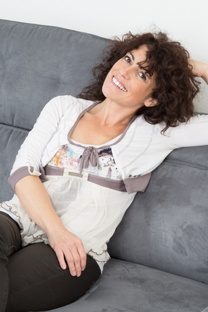woman 40 years: Portrait of charming brunette woman relaxing in sofa