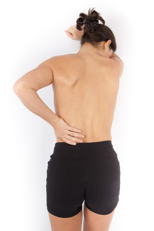 spinal conditions: Woman touching her back in a medical room isolated on white Stock Photo