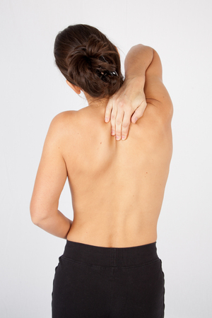 back sprains: Woman touching her back in a medical room isolated on white Stock Photo