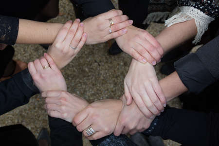 altogether: Close up of hands that hold together outside Stock Photo