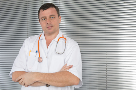 frontal portrait: Frontal portrait of doctor with stethoscope with arms crossed Stock Photo