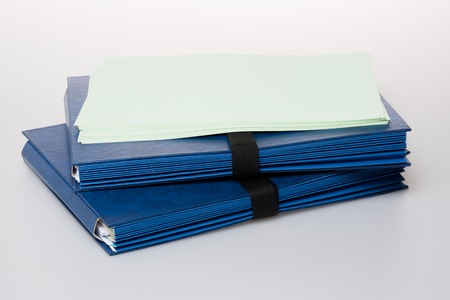 labelled: Folders full of business papers: bills, accounts receivable,invoices,receipts,etc. Blue folder with a business paperwork and red tape.
