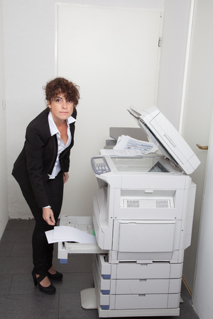 xerox: Woman copying notes on a coin operated photocopier