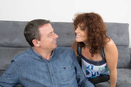 cocooning: In love couple looking at each other on sofa at home