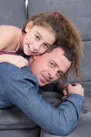 one parent: Smiling father and his daughter doing piggy-back on a sofa Stock Photo