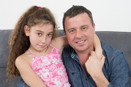 sit around: Girl hugging her father, at home on sofa