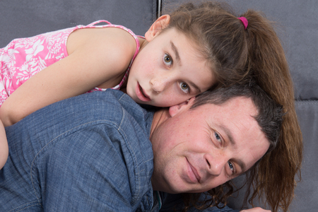 accomplices: Portrait of a man and a girl on sofa - parents and child