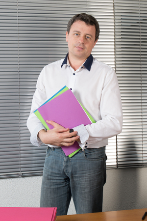 account executive: Business man holding some files. Man wearing a shirt ready for a meeting and holding document files.