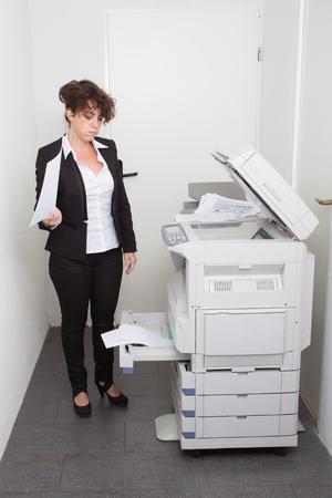 fotocopiadora: Notas Mujer de copiado en una fotocopiadora que funciona con monedas