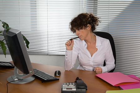 at her desk: Pensive businesswoman working on her laptop at her desk Stock Photo