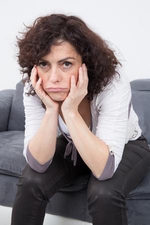 desolaci�n: Mujer infeliz y molesto sentado en el sof� en el fondo blanco Foto de archivo