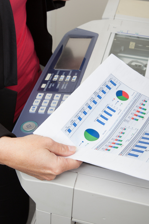 Image of female hand pointing at business document close to a printer