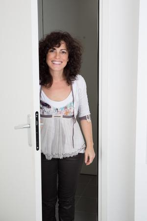 invitando: Mujer alegre que invita a la gente a entrar en la casa