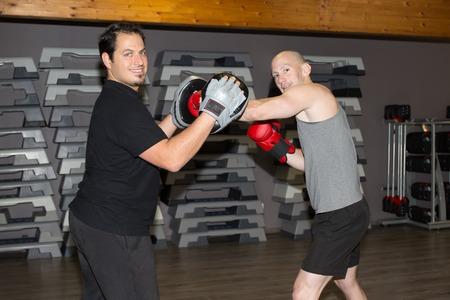 hombres haciendo ejercicio: Retrato de dos hombres de boxeo ejercicio juntos en un gimnasio Foto de archivo