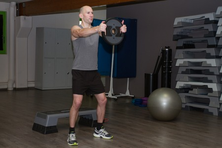 deltoids: Young  man in sporty outfit raising dumbbells to strengthen his deltoids at fitness center