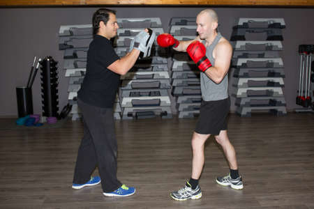 hombres haciendo ejercicio: Two boxing men exercising together at the health club
