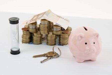 home expenses: Small house and Piggy Bank with Stacks of money  Isolated on a white Background.