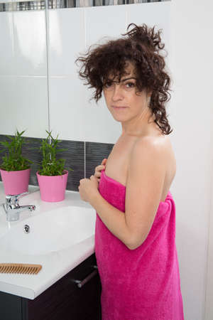 inconvenience: Exhausted woman having a headache in her bathroom at home