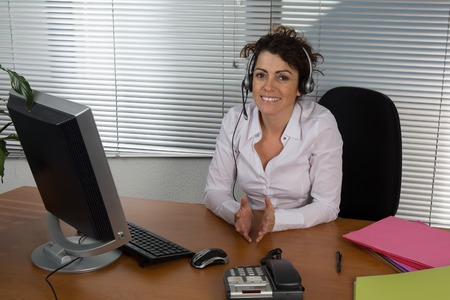 phonecall: Portrait of beautiful customer service representative talking to someone at desk Stock Photo