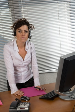 standing reception: Receptionist standing behind reception desk, wearing telephone headset, smiling, portrait