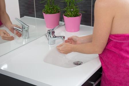 handwash: Woman in her bathroom washing her hands