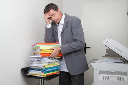 exasperate: Stressed businessman in front of stack of folders at copy machine isolated