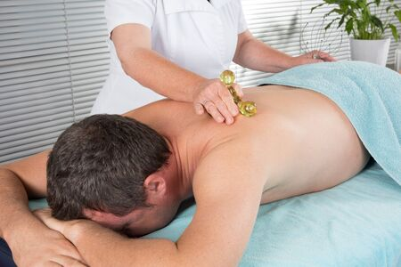 female therapist: Female therapist doing back massage on man body in the spa salon Stock Photo