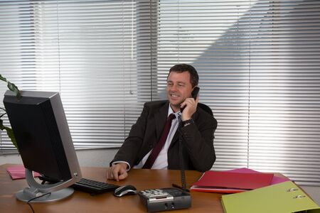 30 35: Portrait of smiling man speaking on  phone, sitting at desk, looking at computer screen.