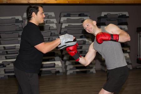thai arts: Caucasian men exercising thai boxing at fitness center