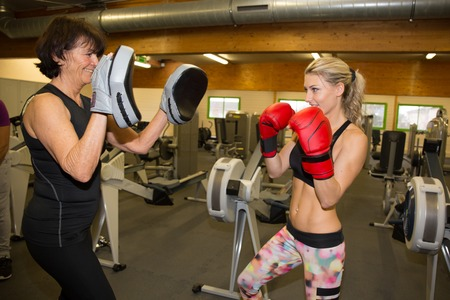 fitnesscenter: Two girls are doing martial arts boxing at gym center Stock Photo