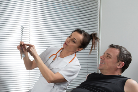 radiologist: Female radiologist and male patient looking at x-ray report