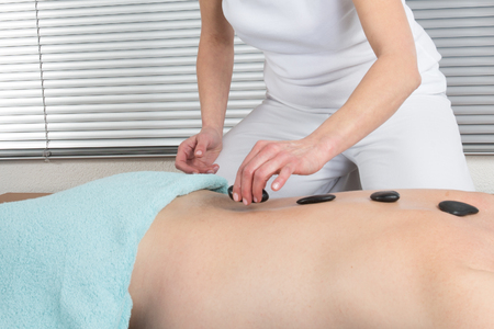 color therapist: Man having a hot stone massage at beauty center