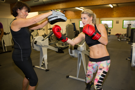 spar: a woman trains with her trainer and is in a punching stance