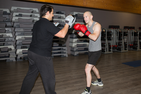 hombres haciendo ejercicio: Caucasian men exercising thai boxing at fitness center
