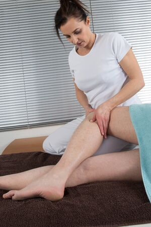 lower limb: Practitioner using his fingers to massage a knee in a room