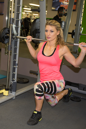 girl squatting: Beautiful girl exercising squatting with barbell