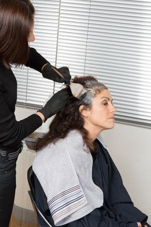 tinte cabello: Destacando el pelo mujer del cliente en un sal�n de peluquer�a peluquer�a Foto de archivo