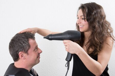 cute blonde: Female hairdresser drying her male customers hair in her hairdressing salon Stock Photo