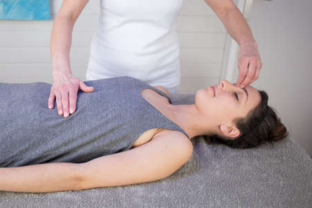 exert: Woman having a facial massage in a spa with the therapist using her fingertips to exert pressure on the forehead for relaxation