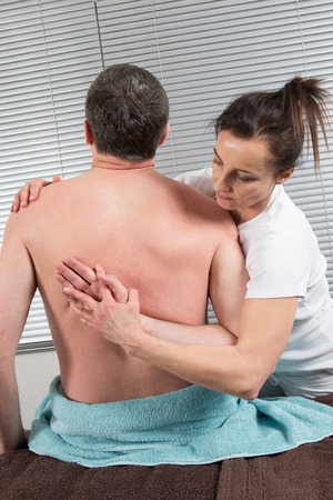 Chiropractor massage the male patient spine and the back