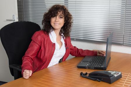 female architect: Female architect using computer, looking to camera