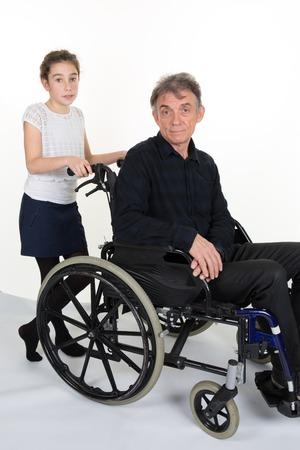 personne malade: Fille poussant l'homme dans un fauteuil roulant - p�re ou grand-p�re