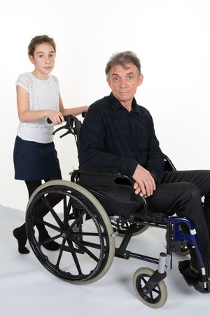 grand father: Girl pushing man in a wheelchair - father or grand father Stock Photo