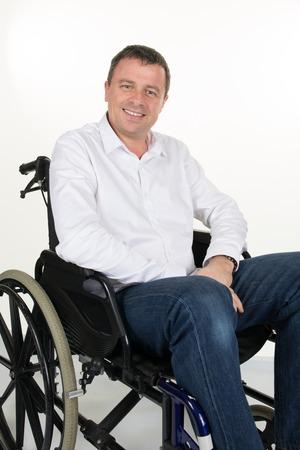paraplegico: Hombre feliz en una silla de ruedas aislado en un fondo blanco Foto de archivo