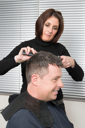 beauty parlour: Hairdresser making haircut to young man at beauty parlour