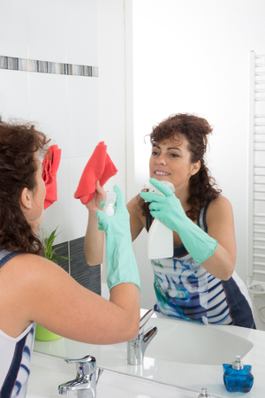 spring cleaning: Cleaning tap -woman is  cleaning a bathroom Stock Photo