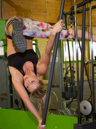 moving activity: Young attractive woman does suspension training  in the gyms studio